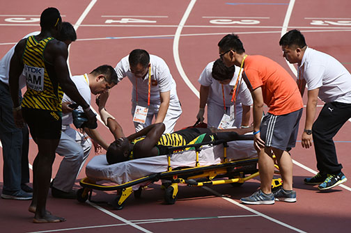 "Jamaica's Javon Francis is helped by medics after getting injured in the qualifying round of the men's 4x400 metres relay athletics event at the 2015 IAAF World Championships at the ""Bird's Nest"" National Stadium in Beijing on August 29, 2015.  AFP PHOTO / GREG BAKER"